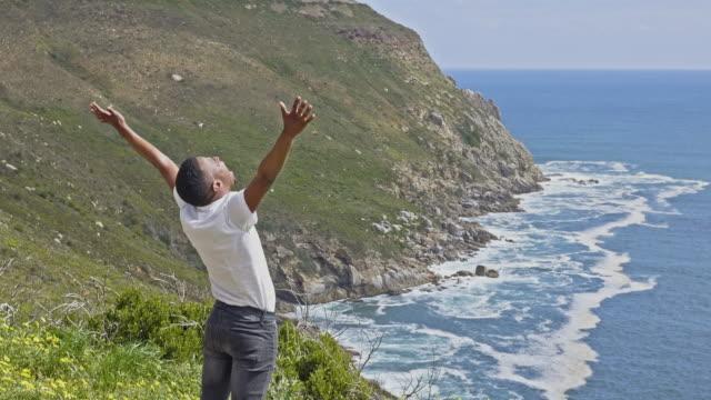 kran-video von jungen afrikanischen mann mit erhobenen armen blick auf den ozean - dankbarkeit stock-videos und b-roll-filmmaterial
