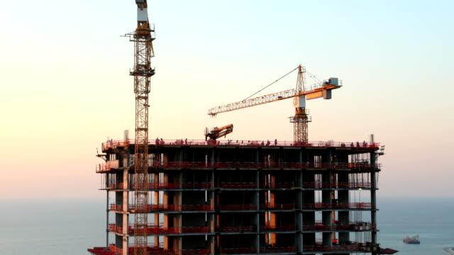 cranes auf einem wolkenkratzer-konstruktion - wolkenkratzer stock-videos und b-roll-filmmaterial