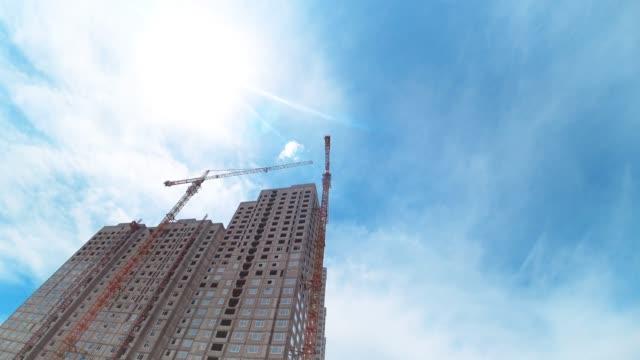 Cranes building house.