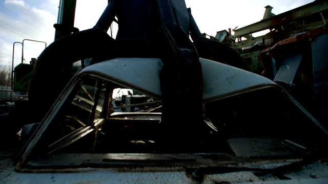 Cranes with hydraulic gripper moving cars for recycling video
