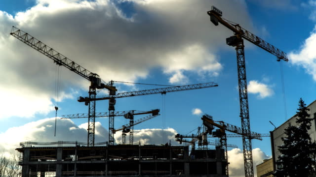 cranes working day and night on construction of the housing estate in former industrial zone, time lapse - industria edile video stock e b–roll