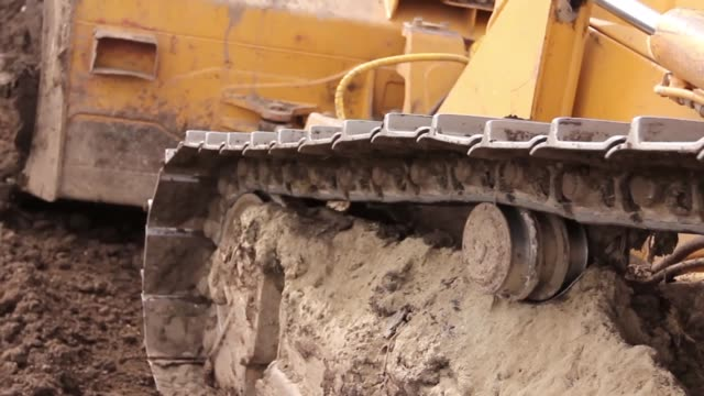 Crawler's tracks, bulldozer machine is leveling construction site Close up view on bulldozer's undercarriage during pushing ground at construction site. H.264 video codec civil engineering stock videos & royalty-free footage
