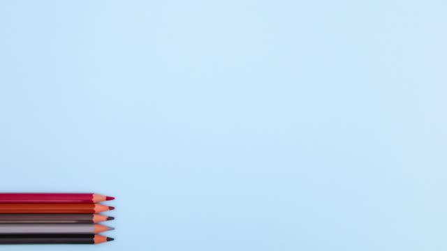 i pastelli appaiono e scompaiono sul lato sinistro dello sfondo blu pastello - stop motion - arti e mestieri video stock e b–roll