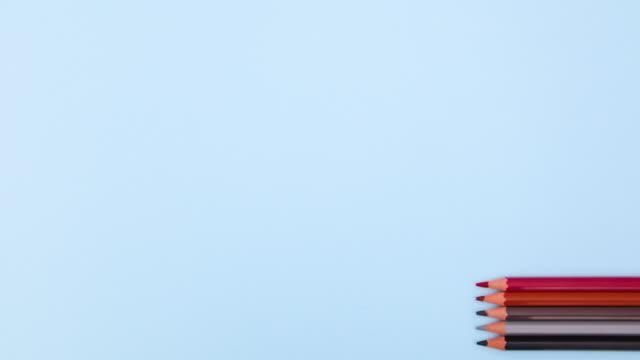 蠟筆出現在柔和的藍色背景的右側並消失 - 停止運動 - back to school 個影片檔及 b 捲影像