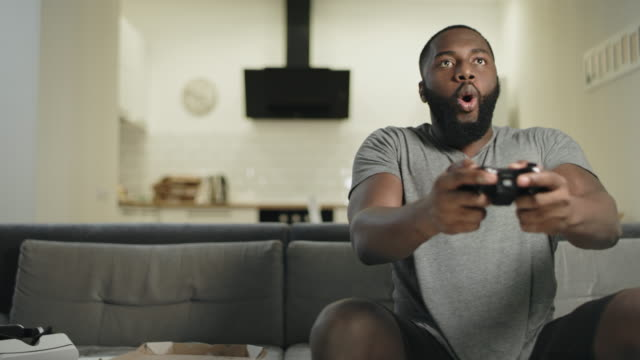 crazy black man playing video game at home kitchen. - gaming filmów i materiałów b-roll