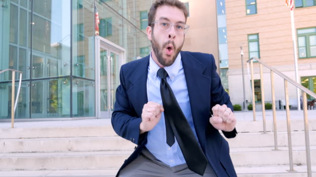 crazy businessman celebrating and silly dancing outside office building - tiktok стоковые видео и кадры b-roll