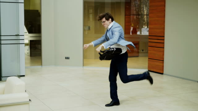 crazy businessman dancing with briefcase in modern lobby while his colleagues walking and watching him surprised - men filmów i materiałów b-roll