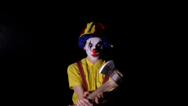 A crazy clown plays with an axe. video
