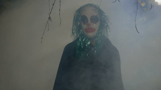 Crazy evil halloween clown coming up from a foggy wood and doing a ritual dance to frighten people video