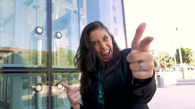 A crazy female business executive doing a victory dance and pointing