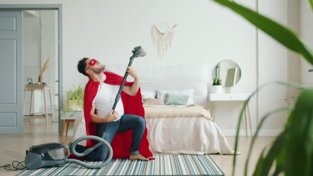 Crazy guy in superman costume dancing with vacuum cleaner having fun indoors Crazy guy in superman costume is dancing with vacuum cleaner having fun indoors vacuuming carpet in bedroom. Funny people, super hero and lifestyle concept. rock music stock videos & royalty-free footage