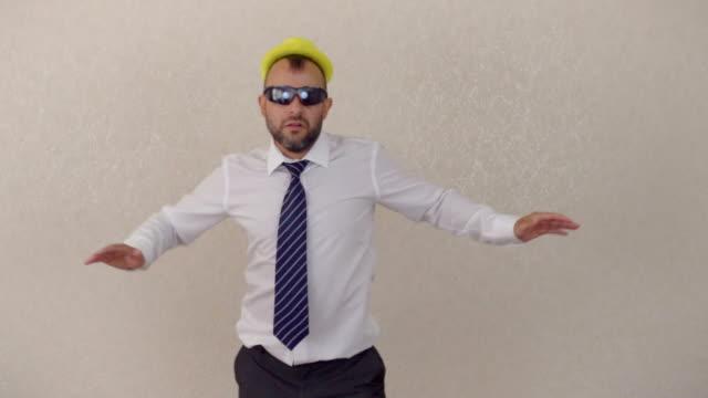 crazy happy businessman dancing in corporate office wearing suit celebrating achievement - дикая растительность стоковые видео и кадры b-roll