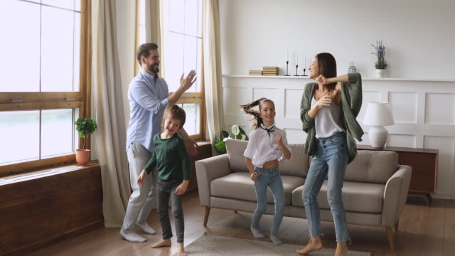 stockvideo's en b-roll-footage met gekke gelukkige ouders en kinderen dansen springen in de woonkamer - vier personen