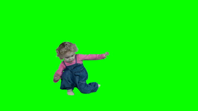 crazy little child girl romp dance move isolated on green - stare in piedi video stock e b–roll