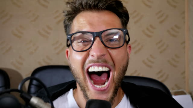 crazy male in eyeglasses with wide open mouth screams into microphone at recording studio video