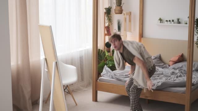 Crazy man dancing in bedroom at home