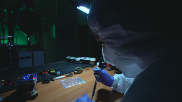 Crazy man making improvised explosive device, soldering in illegal laboratory