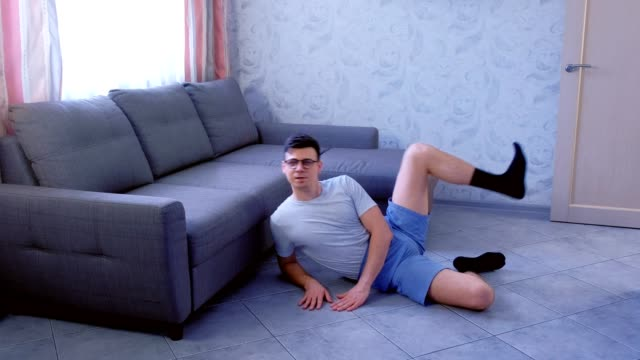 Crazy nerd man is doing funny shaping exercises for legs laying on the floor at home. Sport humor concept. video