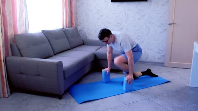 çılgın adam evde mat üzerinde ilk kez böler yapmaya çalışıyor ve düşüyor. spor mizah konsepti. - bölmek stok videoları ve detay görüntü çekimi