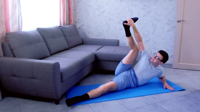 Crazy nerd man is trying to stretch his legs laying on the mat at home. Sport humor concept. video