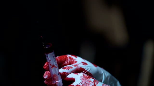 Crazy nurse holding a syringe with blood in hands, horror scene, close up video