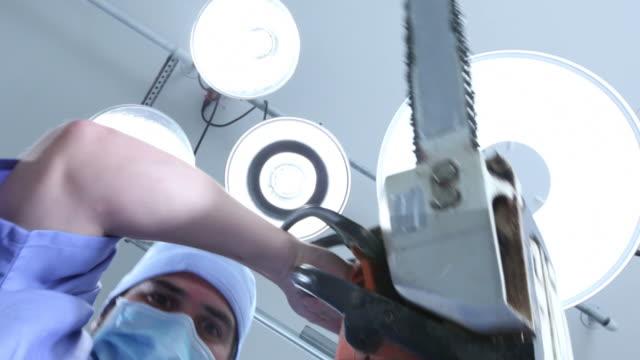 crazy chirurgo avvio da sega elettrica - motosega video stock e b–roll