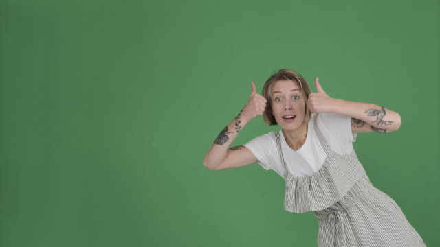 crazy woman giving thumbs up gesture over green background - comparsa video stock e b–roll
