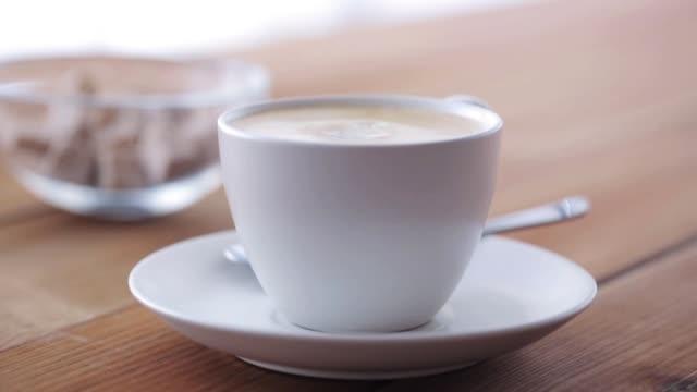 sahne gießen, kaffeetasse auf holztisch - milchkrug stock-videos und b-roll-filmmaterial