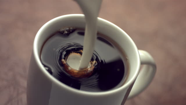 Cream splashing into coffee cup, slow motion video