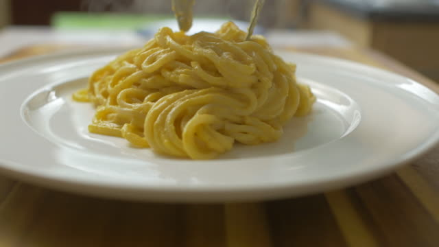 creamy butternut squash linguine with fried sage close up view of putting creamy butternut squash linguine on th plate with fried sage leaves spaghetti stock videos & royalty-free footage
