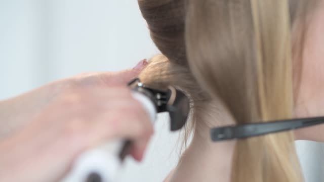 create hairstyles using hair spray. beautiful curls at the blonde. - длина стоковые видео и кадры b-roll
