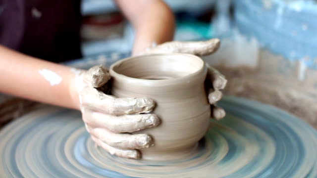 Creating a clay pot.Potter.Workshop of clay.Clay on the device.Master.Hands working on pottery wheel, shaping a clay pot
