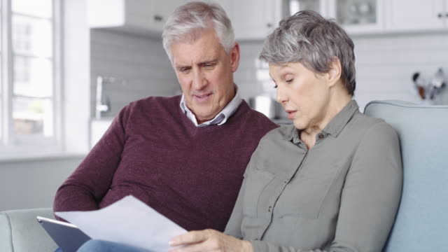 Creating a comprehensive spending plan 4k video footage of a senior couple using a digital tablet while going through paperwork at home bills and taxes stock videos & royalty-free footage
