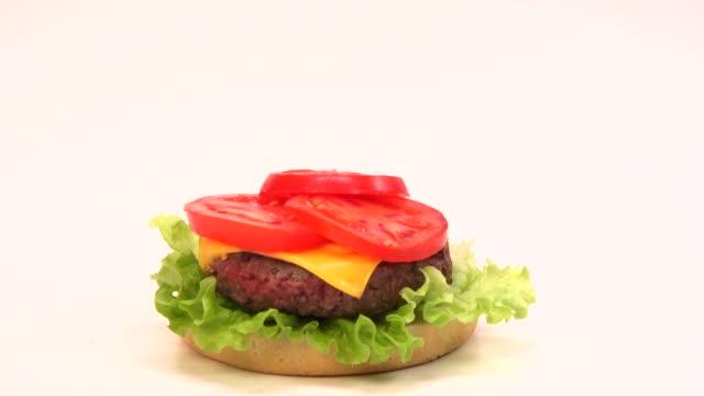 vídeos y material grabado en eventos de stock de creación de una hamburguesa con queso sobre fondo blanco - hamburguesa