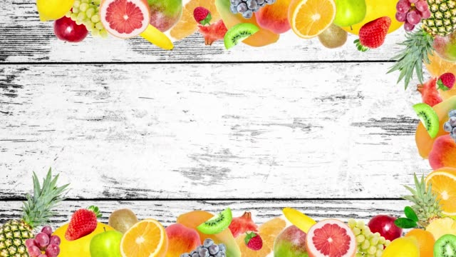 Video Creative 4k stop motion video animation of many different exotic tropical bright fruits frame quickly appearing and disappearing on old grunge vintage wooden background. Seamless loop.