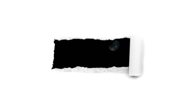 Creative 4k time laps video of a glowing full moon in the night sky with floating clouds, which is visible through a hole with torn edges in white paper.