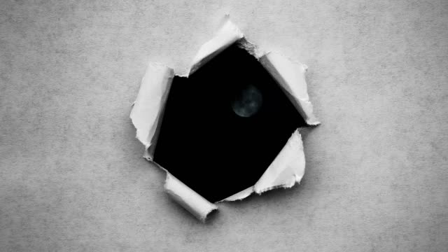 Creative 4k time laps video of a glowing full moon in the night sky with floating clouds, which is visible through a circle hole with torn edges in old retro grunge vintage paper.