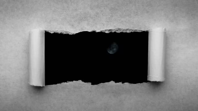 Creative 4k time laps video of a glowing full moon in the night sky with floating clouds, which is visible through a hole with torn edges in old retro grunge vintage paper.