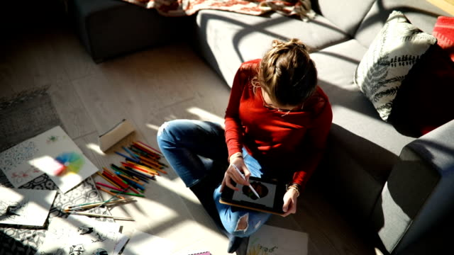 Creative activity at home Young girl drawing on the floor using graphics tablet enjoying her hobby studio workplace stock videos & royalty-free footage
