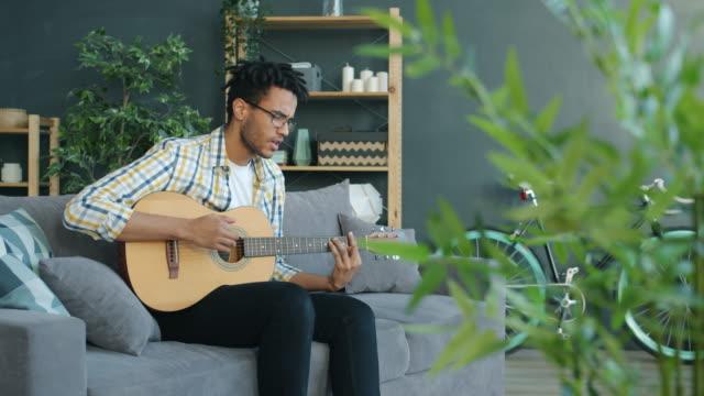 creative afro-amerikansk man spelar gitarr och sjunger på fritiden hemma - akustisk gitarr bildbanksvideor och videomaterial från bakom kulisserna