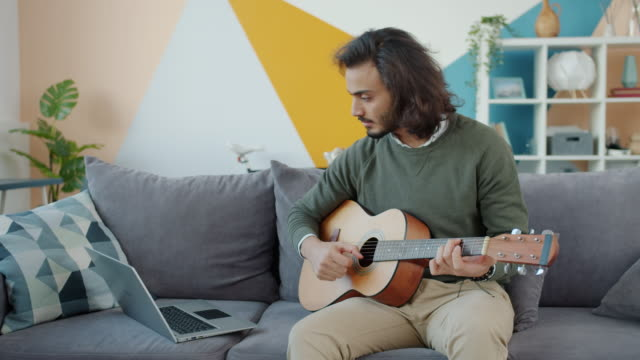 Creative Arab man playing the guitar and using laptop watching tutorial at home video