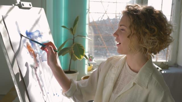 vidéos et rushes de inspiration créative artiste, femme artisan heureux avec muse peintures photo avec des couleurs vives sur toile blanche sur chevalet à l'intérieur - toile à peindre