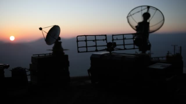 Video Creative artwork decoration. Silhouette of mobile air defence truck with radar antenna during sunset. Satellite dishes or radio antennas against evening sky. Selective focus