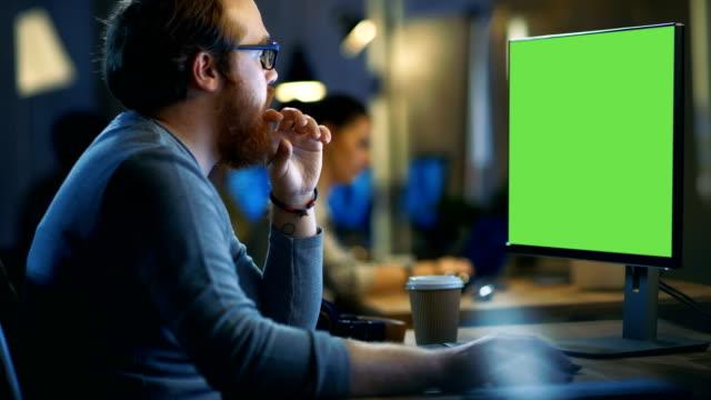 kreative bärtiger mann arbeitet auf einem pc mit isolierten mock-up green screen. seine bürofläche ist modern und cool. - mann bart freisteller stock-videos und b-roll-filmmaterial