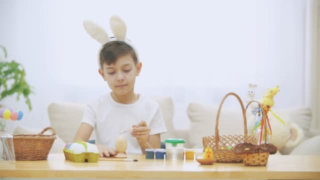 Creative boy is colorizing an Easter egg with a help of paint-brush., wearing bunny ears, then raises his thumb fingers up.