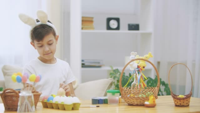 Creative boy is colorizing an Easter egg with a help of paint-brush., wearing bunny ears, then he takes a wooden basket and shows how many coloured Easter eggs there are.
