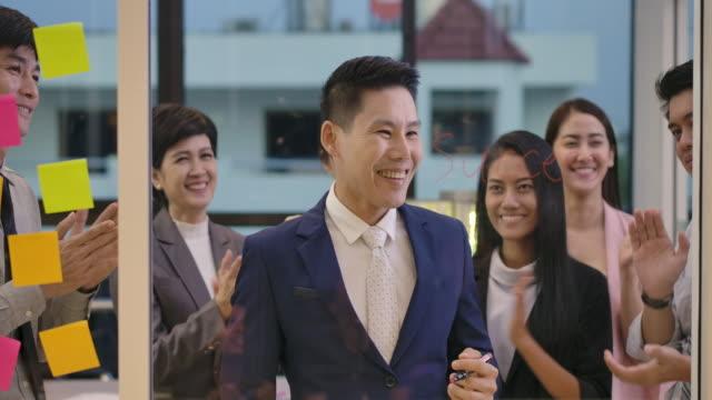 kreatives business-team brainstorming und austausch von ideen mit haftnotizen auf glaswand zusammen. konzept der strategieentwicklung, analyseplanung und kreativität. - post it stock-videos und b-roll-filmmaterial
