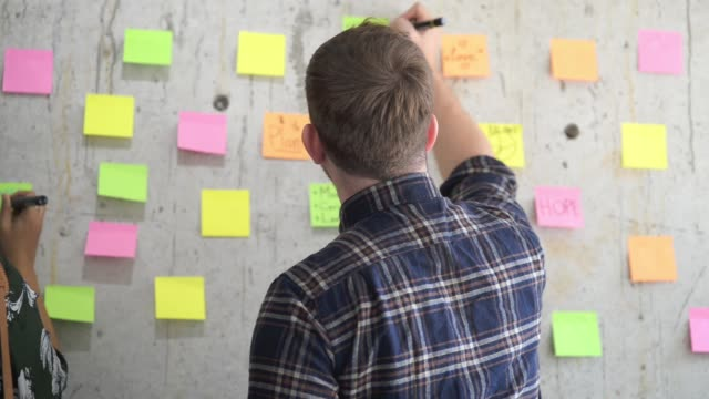 vídeos de stock e filmes b-roll de creative business team generating ideas and writing them down on adhesive notes attached to the cement wall - papel adesivo