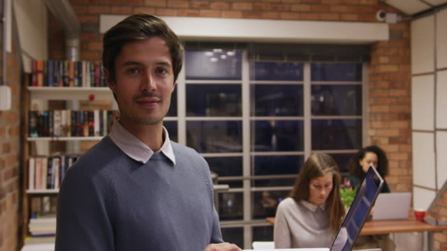 vídeos de stock e filmes b-roll de creative businessman with laptop smiling in modern office - trabalho de design