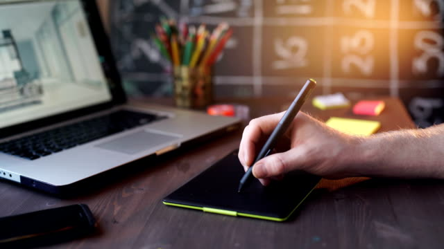 Creative businessman writing on graphic tablet while using laptop in office video